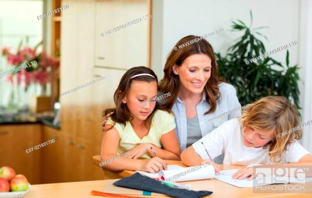 Stock Photo: Mother having a look at children&#039 s homework.