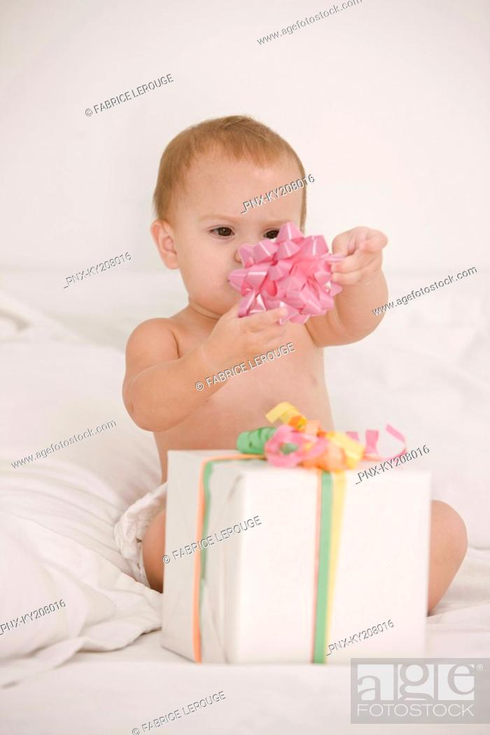 Stock Photo: Baby girl playing with a bow on the bed.