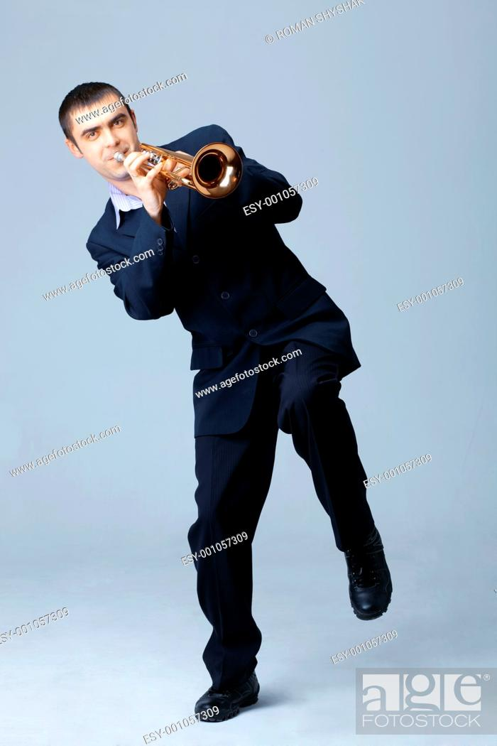 Stock Photo: Adult man in suit playing on trumpet.