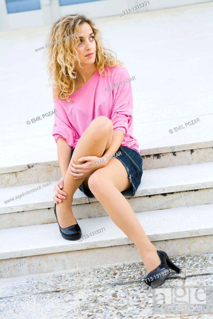 Stock Photo: Pretty young woman is sitting low on steps.