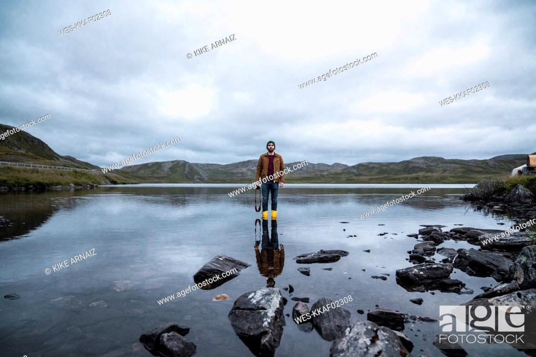 Stock Photo: Young man standing ankle deep in water, holding camera.