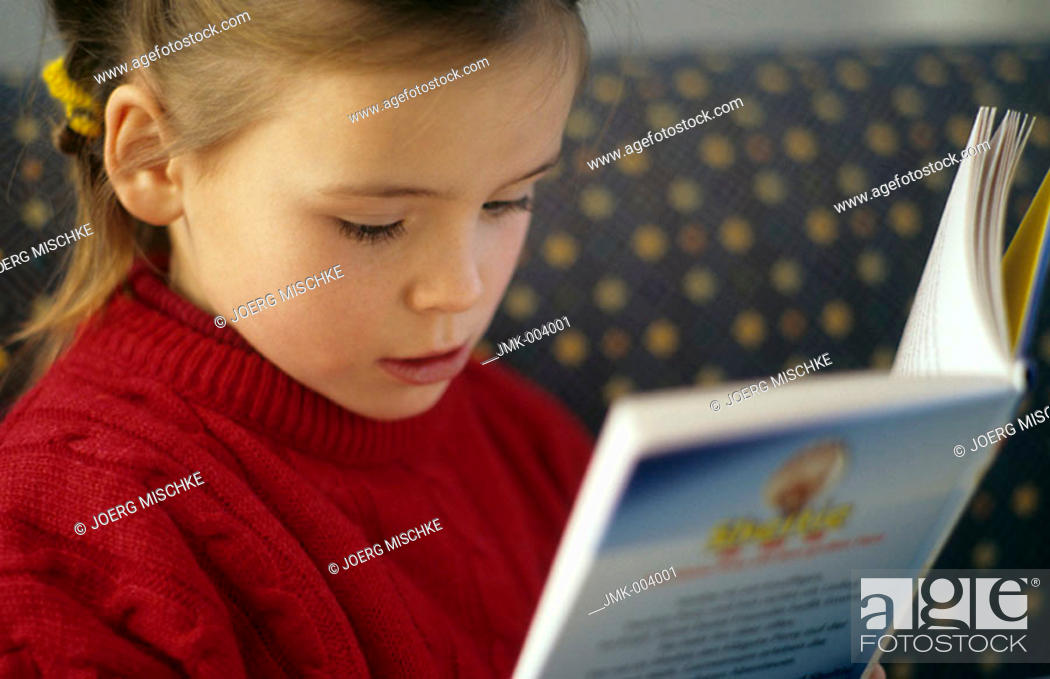 Stock Photo: A little girl, 5-10 years old, reading a book.