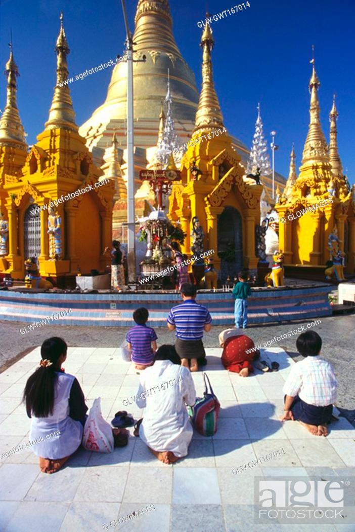 Stock Photo: Rear view of pilgrims praying in front of a pagoda, Shwedagon Pagoda, Yangon, Myanmar.