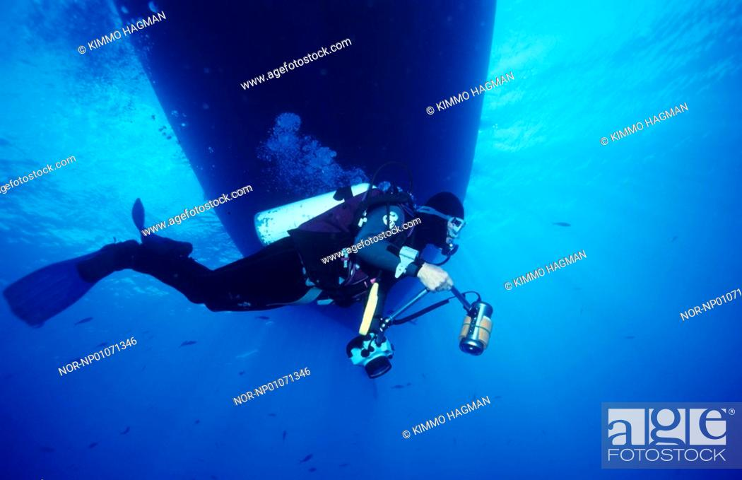 Stock Photo: Scuba diver holding an underwater camera and swimming underwater.