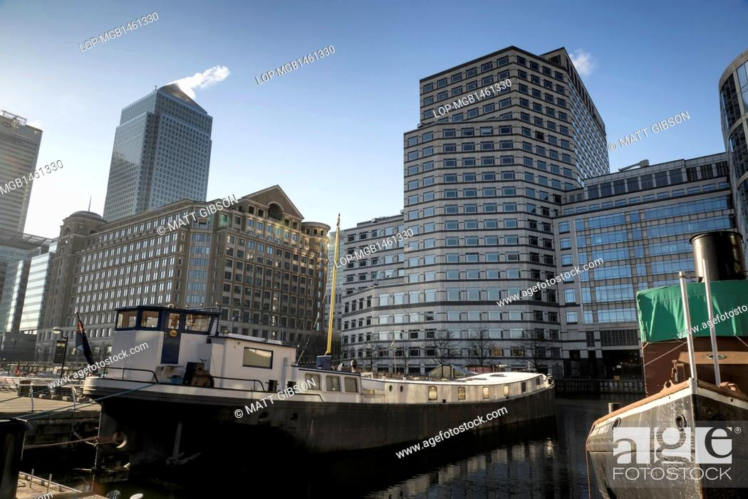 Stock Photo: England, London, Canary Wharf. Boats in docks overshadowed by One Canada Square in the early morning.