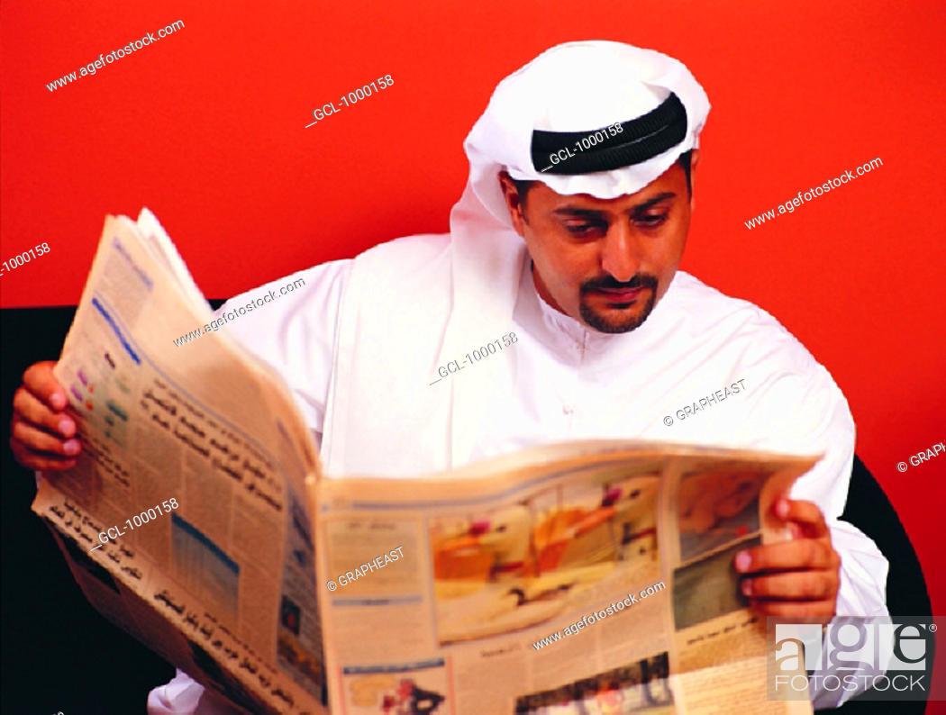 Stock Photo: Arab man reading newspaper.