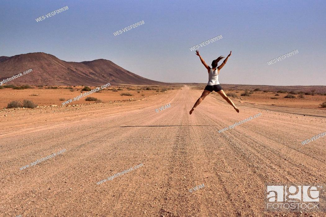 Stock Photo: Woman jumping in the middle of a dirt road, Damaraland, Namibia.
