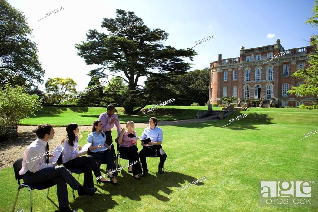 Stock Photo: Businessmen and women with folders in grounds by manor house.