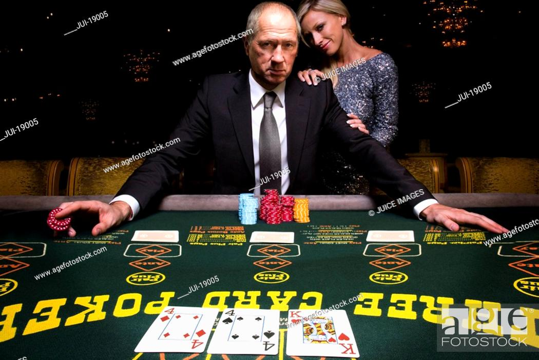 Stock Photo: Woman by man gambling at poker table, portrait, elevated view.