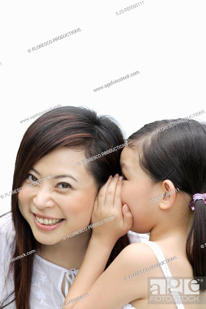 Stock Photo: Young girl indoors whispering in woman's ear.