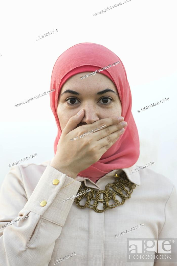 Stock Photo: Muslim woman covering mouth with hand.