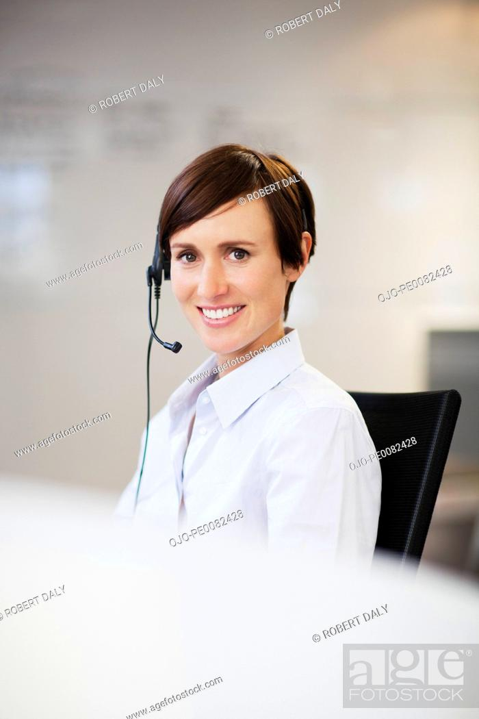 Stock Photo: Portrait of smiling businesswoman wearing headset.