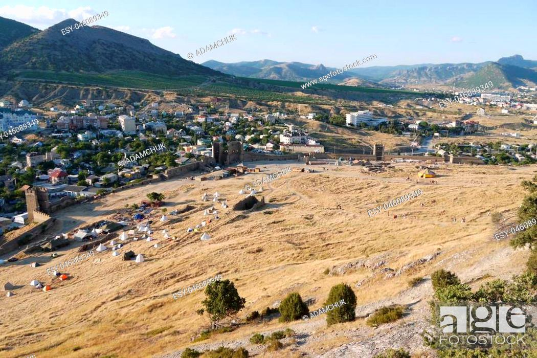 Stock Photo: a small cozy town surrounded by high grassy slopes on a blue sky background.