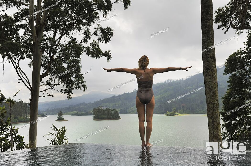 Stock Photo: young woman standing on the edge of the swimming pool of the Summerville Bungalow overlooking the Castlereagh Lake, luxury Ceylon Tea Trails resort, near Hatton.