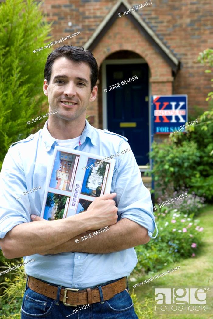 Stock Photo: Young man with magazine outside house with 'for sale' sign, smiling, portrait.