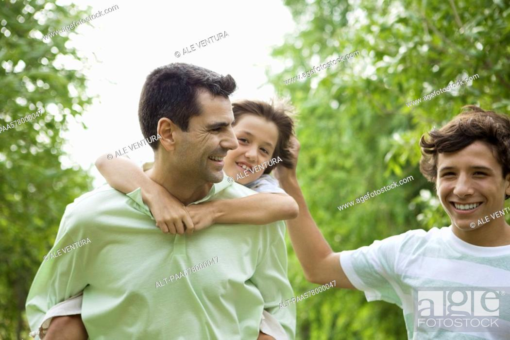 Stock Photo: Father and sons having fun together outdoors.