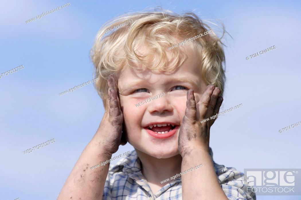 Stock Photo: Germany, Bavaria, Boy playing with charcoal, smiling.