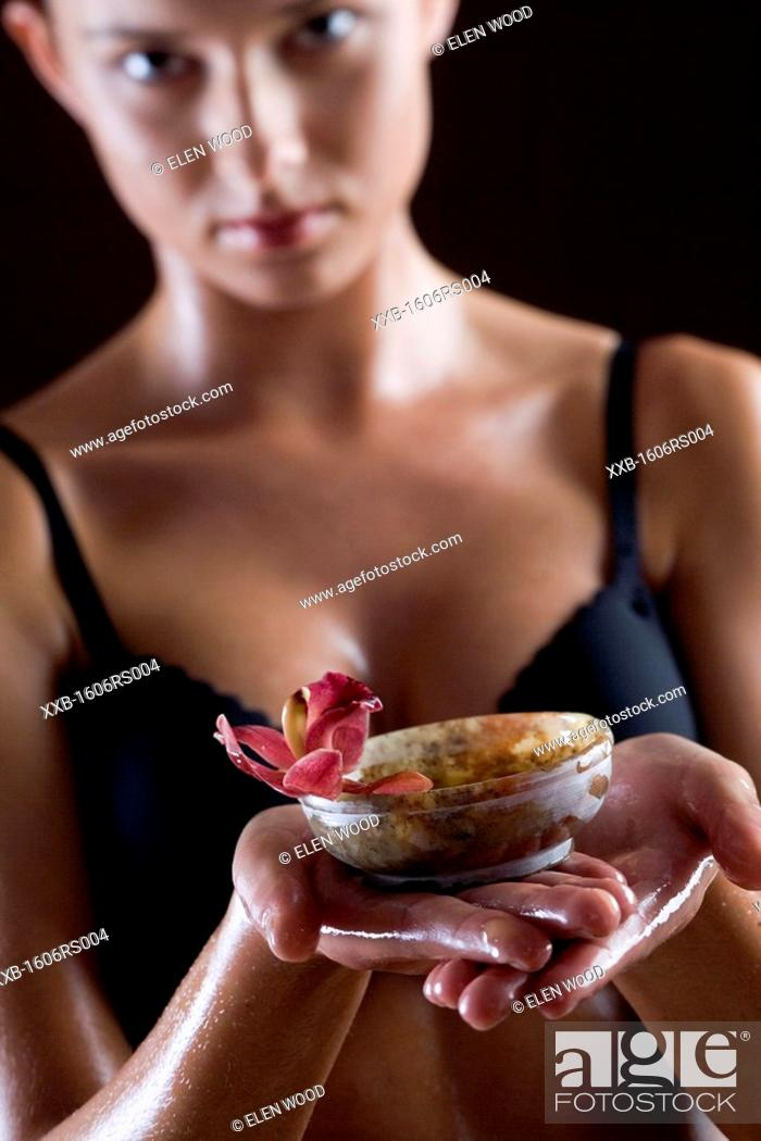 Stock Photo: woman holding bowl with flower oil.