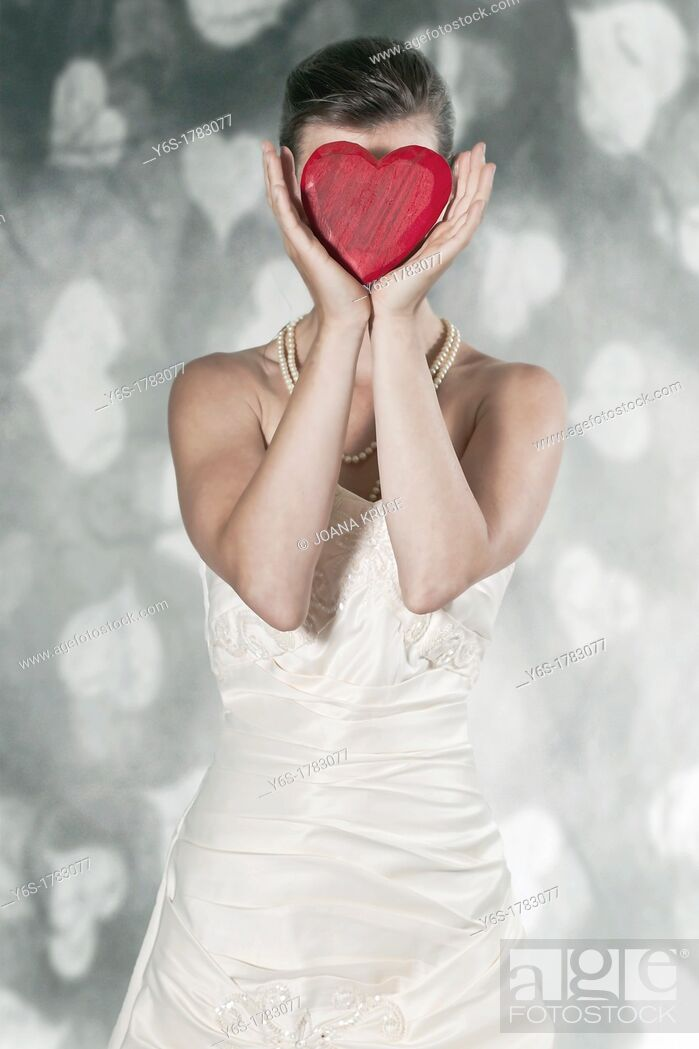 Stock Photo: a woman in a wedding dress holding a heart in front of the face.