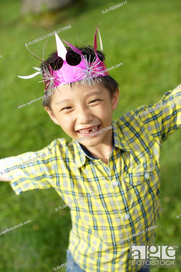 Stock Photo: Young boy outdoors wearing party hat.