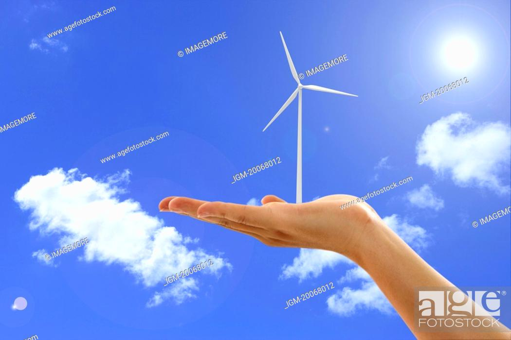 Stock Photo: Lohas, Environmental Conservation, Digitally generated image of human hand holding a windmill in blue sky.