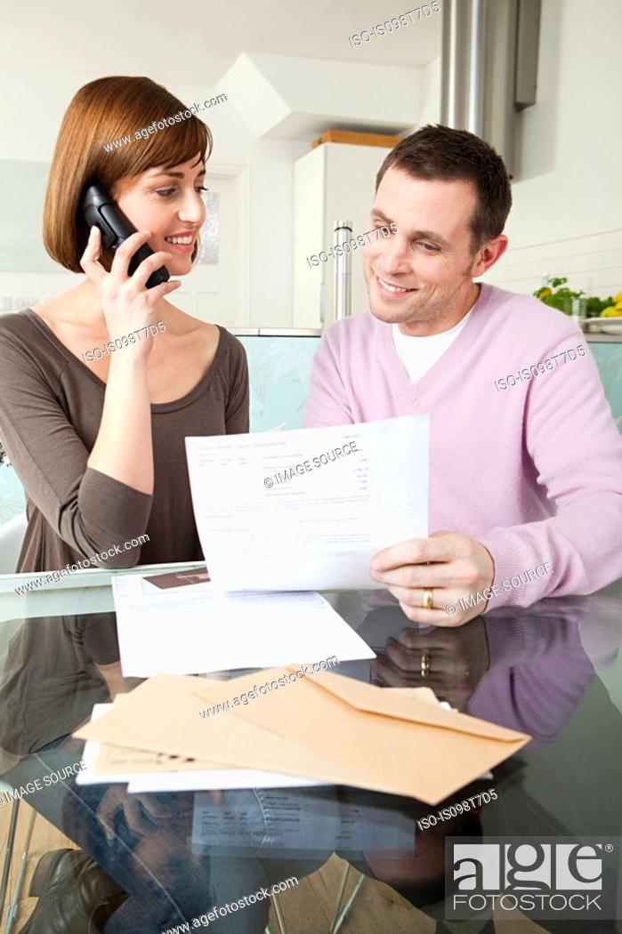 Stock Photo: Couple on telephone with bills.