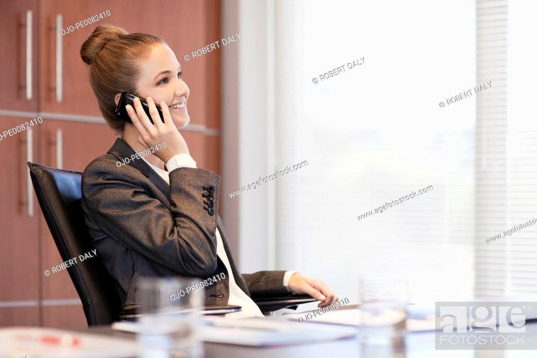 Stock Photo: Smiling businesswoman talking on cell phone at desk in office.