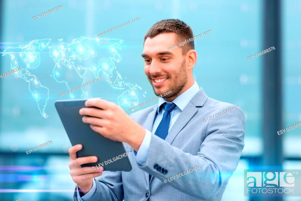 Stock Photo: global business, education, technology and people concept - smiling businessman working with tablet pc computer and world map hologram on city street.