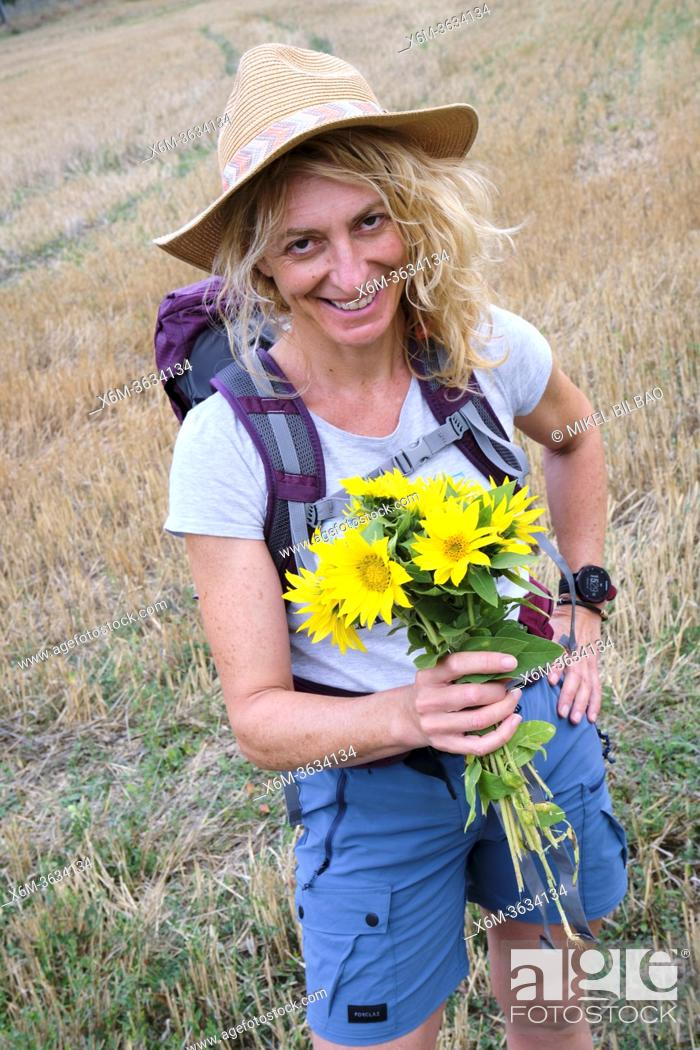 Stock Photo: Mature young woman with a sunflowers bunch in outdoor. Frias town, Burgos, Castile and Leon, Spain.