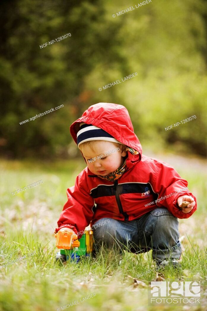Stock Photo: A little girl playing with a toy car outdoors.