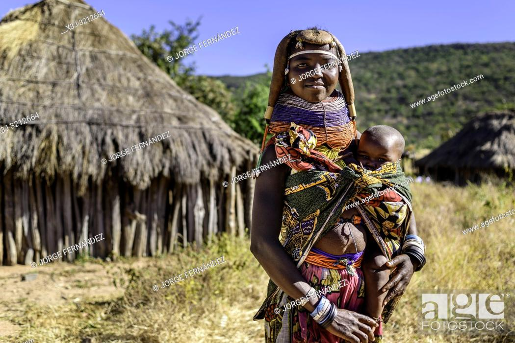 Stock Photo: Portrait of a Muila woman with traditional ornaments and hairstyle carrying a child.