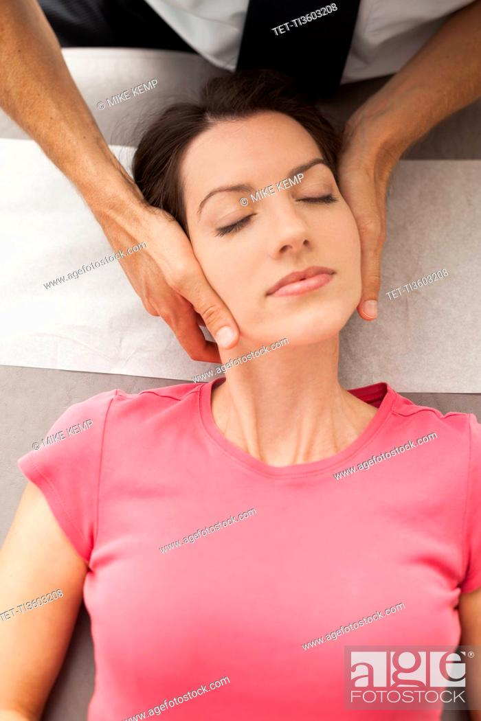 Stock Photo: Woman laying down getting neck adjusted by chiropractor.