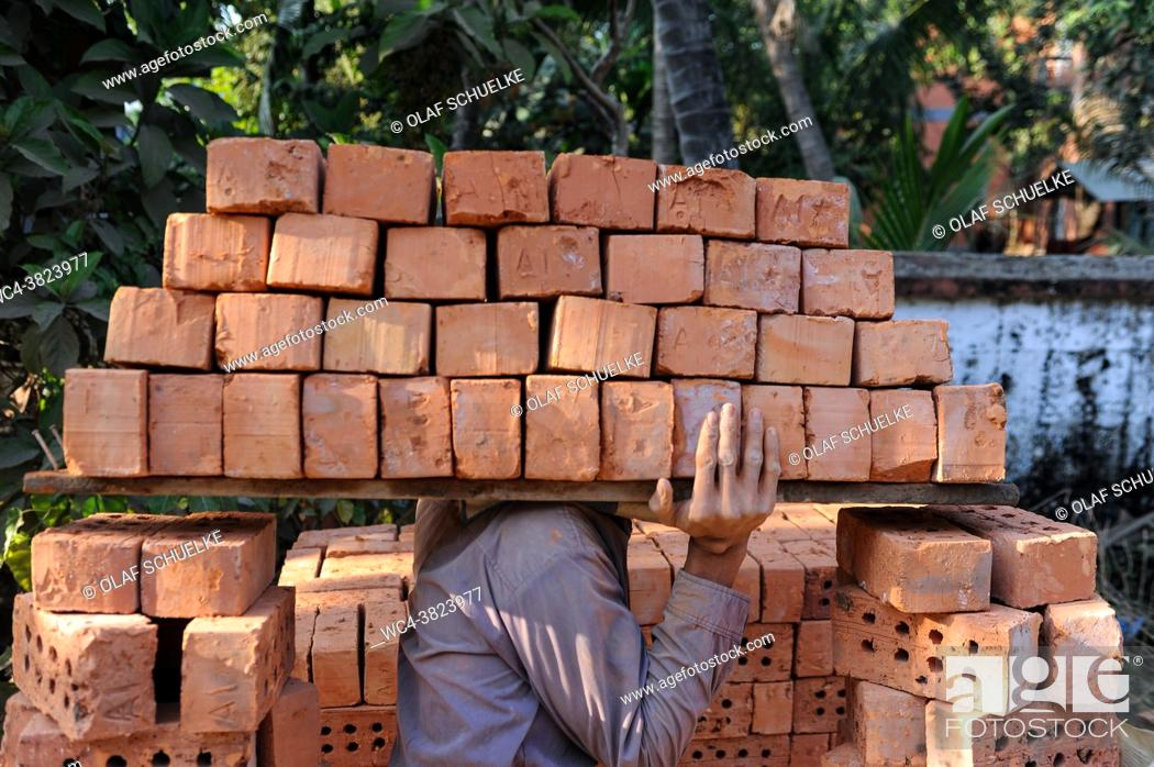 Stock Photo: Yangon, Myanmar, Asia - A construction worker carries a stack of bricks on his shoulder to a nearby building site.