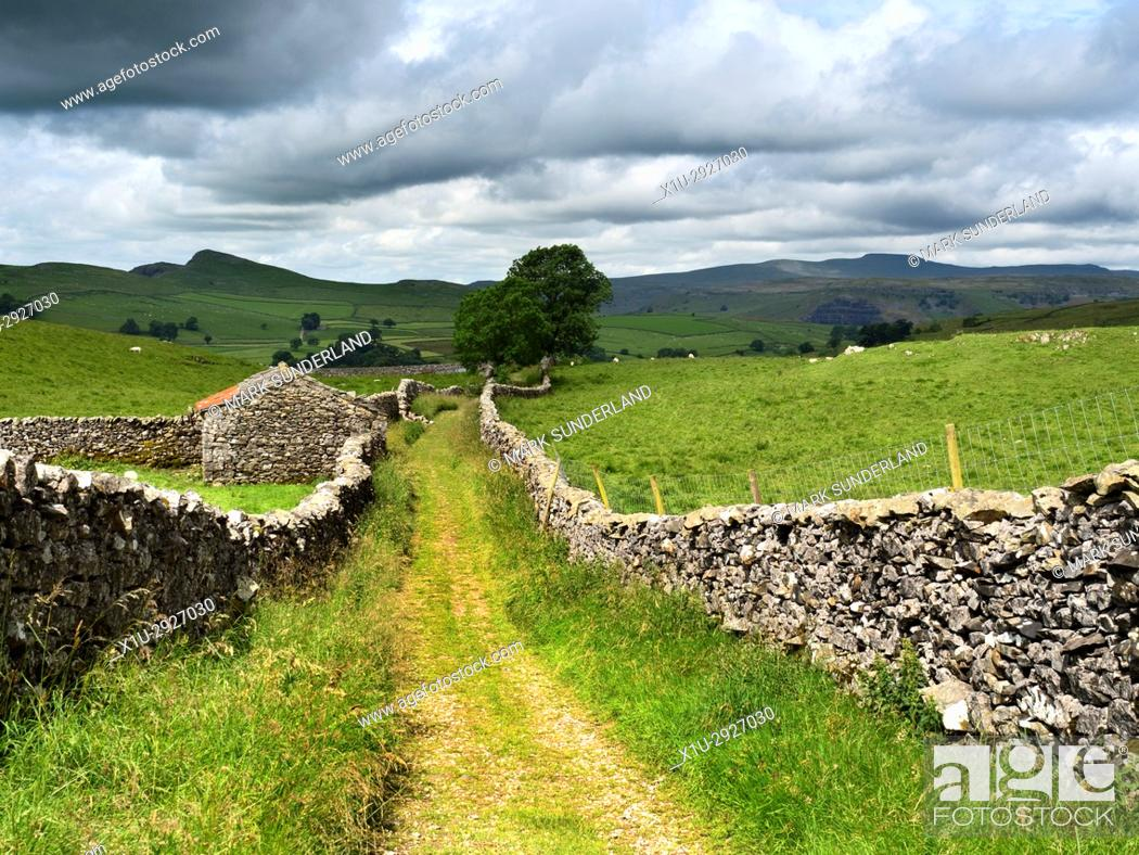 Stock Photo: View down Goat Scar Lane above Stainforth to Smearsett Scar and Ingleborough Stainforth Ribblesdale Yorkshire Dales England.