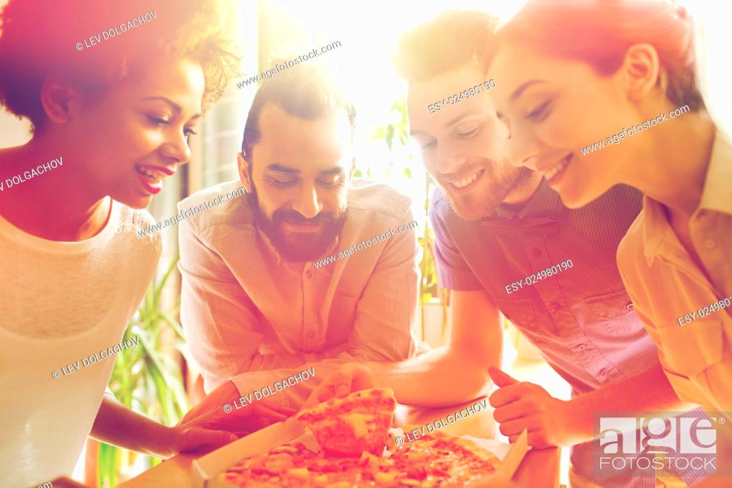 Stock Photo: business, food, lunch and people concept - happy business team eating pizza in office.