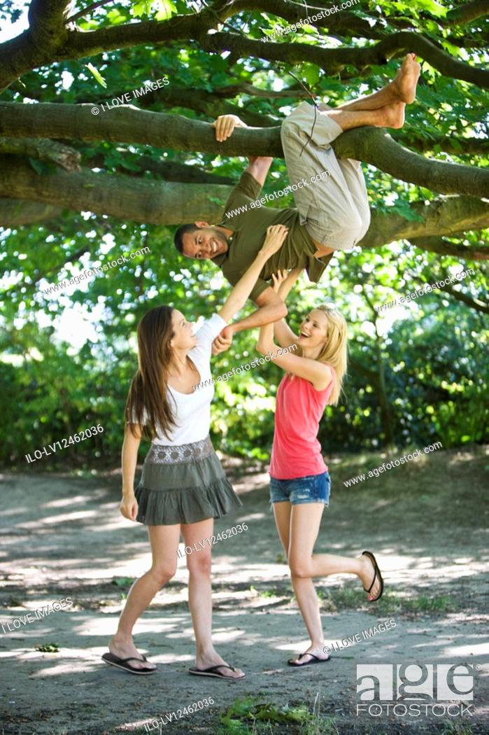Stock Photo: A young man hanging from a tree, two female friends tickling him.