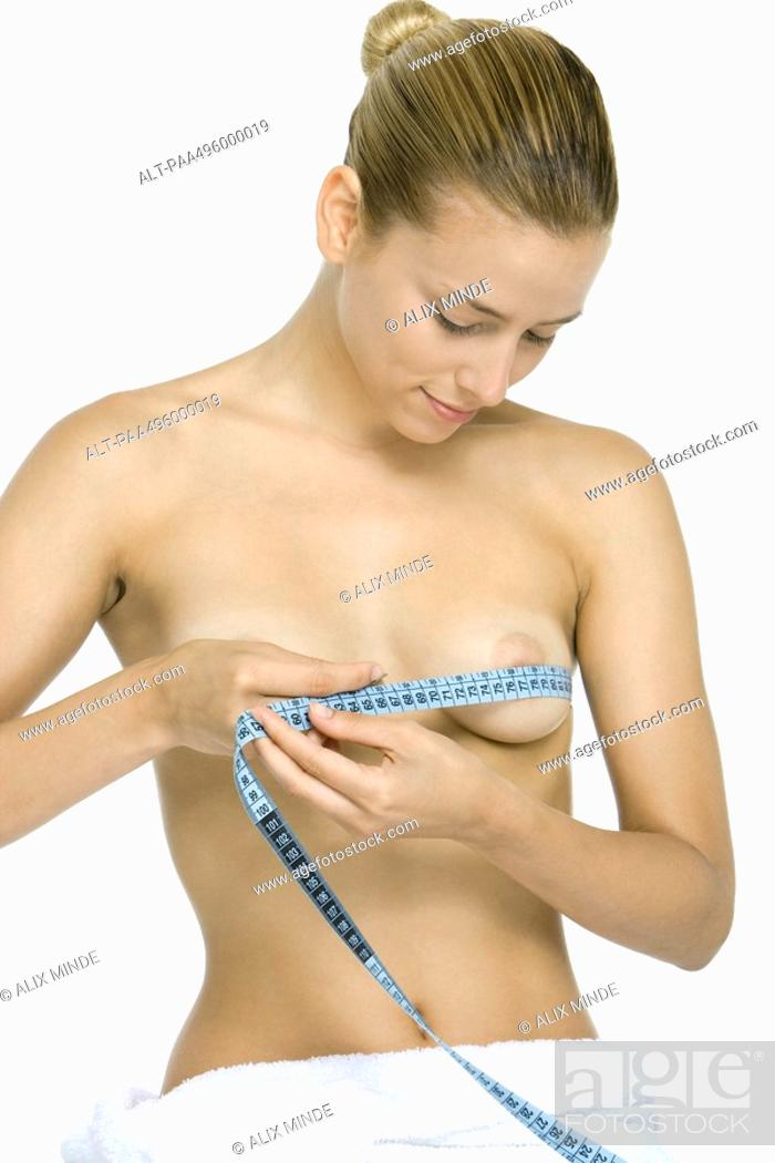 Stock Photo: Woman wrapping measuring tape around chest, looking down at breasts, smiling.