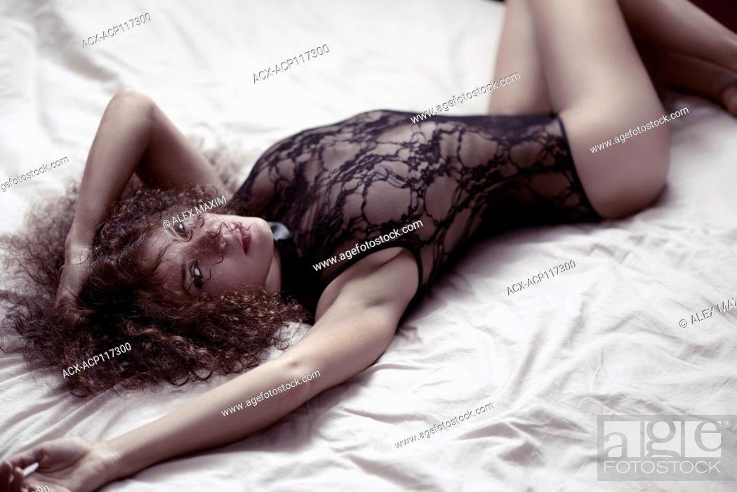Stock Photo: Sensual boudoir portrait of a sexy young beautiful woman lying on a bed in lacy underwear looking at camera.