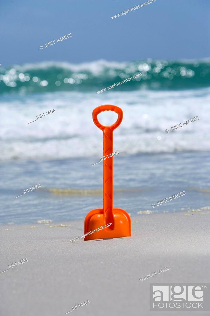 Stock Photo: Red spade in sand on beach.