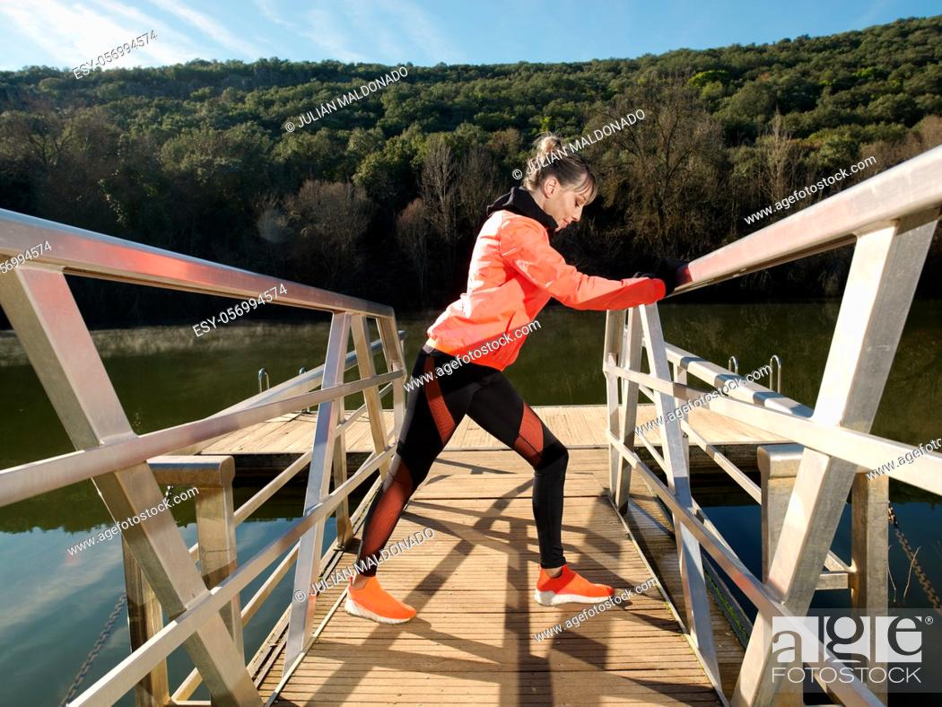 Stock Photo: Young athlete woman exercises and stretches on the platform of a river.