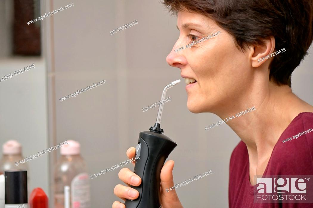 Stock Photo: Portrait Of A Young Womanand and Professional Oral Irrigator or Flosser.
