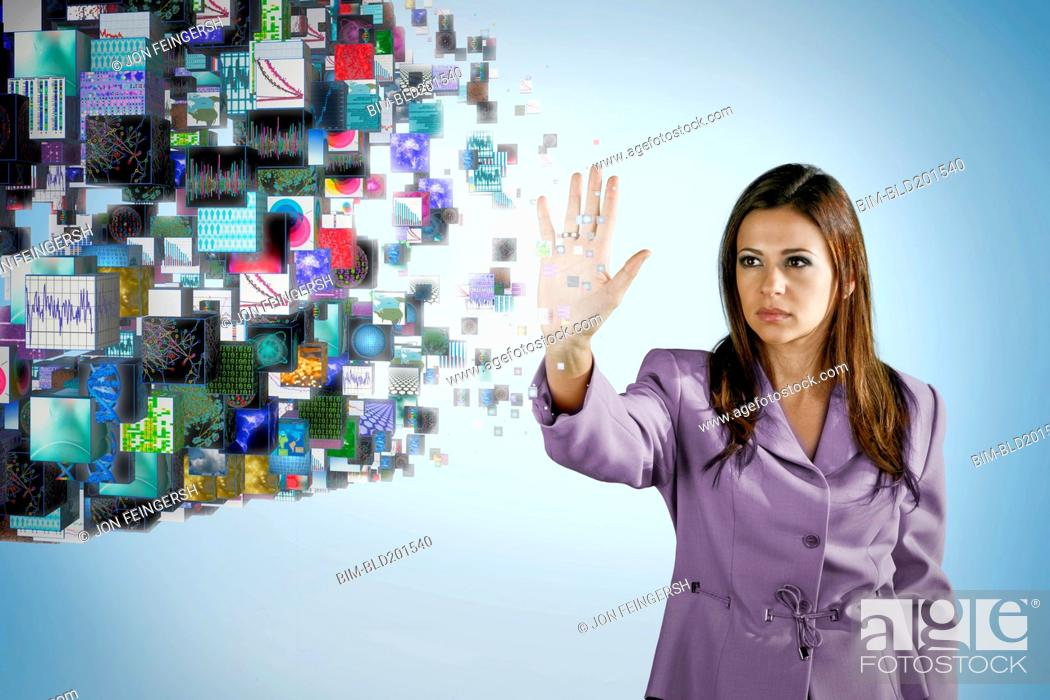 Stock Photo: Businesswoman holding hand out toward digital images.