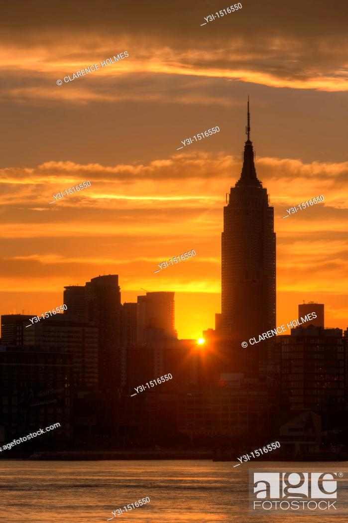 Stock Photo: The rising sun shines between Manhattan buildings including the Empire State Building just after sunrise, New York City, New York, USA.