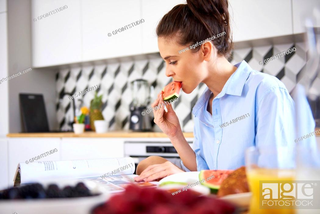 Stock Photo: Young woman at home in kitchen, eating breakfast, reading book.