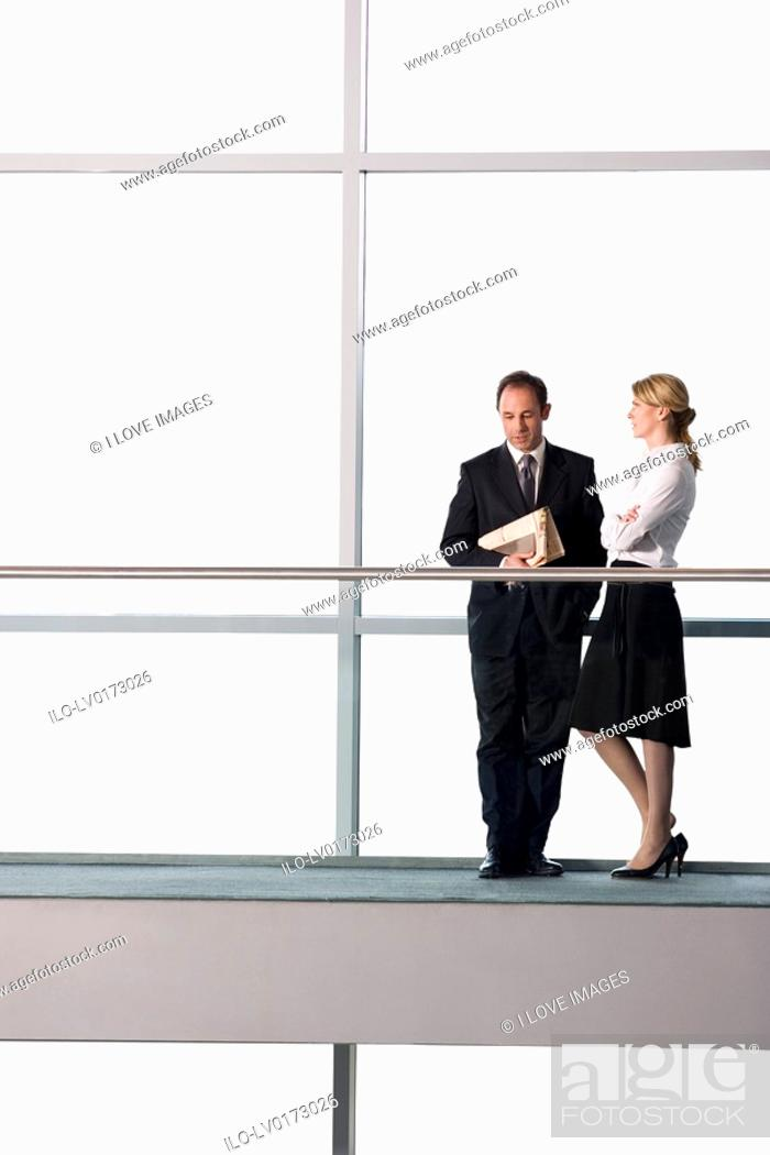 Stock Photo: Businessman and woman talking in modern office building.