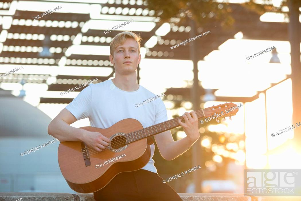 Imagen: Young musician playing guitar in park.