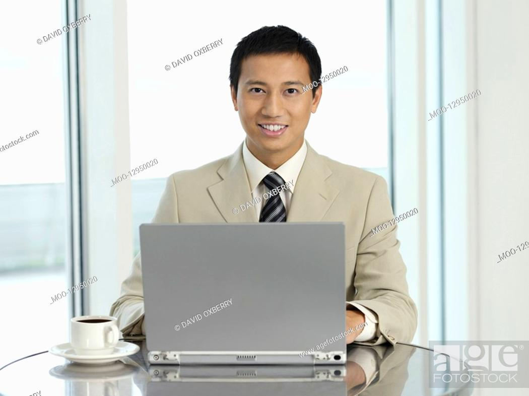 Stock Photo: Businessman sitting at table working on laptop portrait.