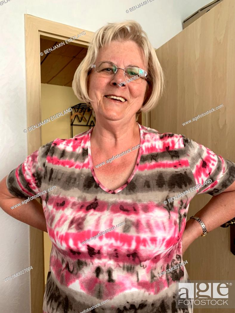 Stock Photo: positive senior woman with arms akimbo at home, in Cottbus, Germany.