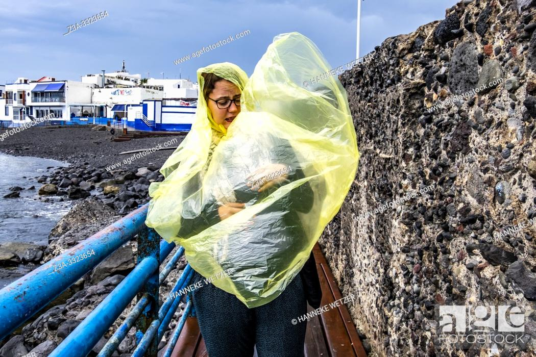 Stock Photo: Girl with yellow poncho during a storm in Agaeta, Gran Canaria.