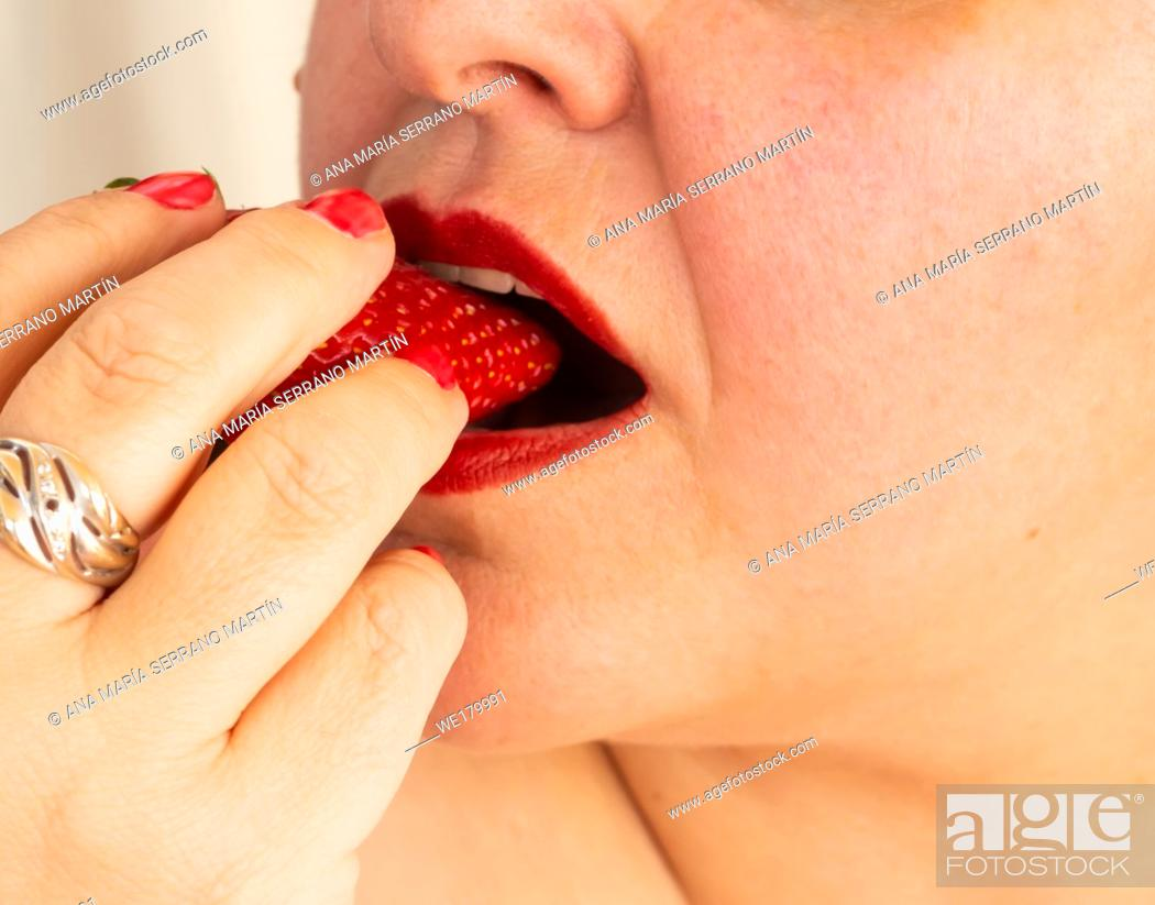 Imagen: An adult woman with red nails and lips eating a strawberry.